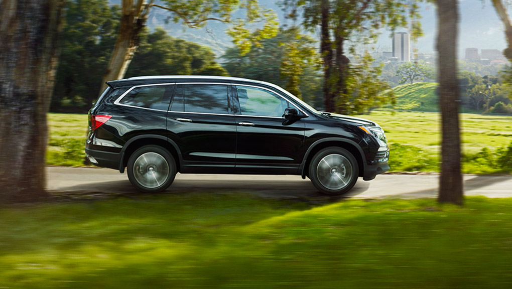 A 2019 Honda Pilot drives confidently down a country road