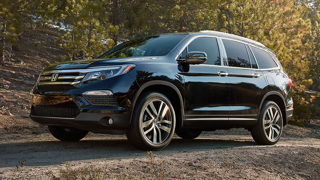 A 2019 Honda Pilot is proudly parked on a forested road in autumn