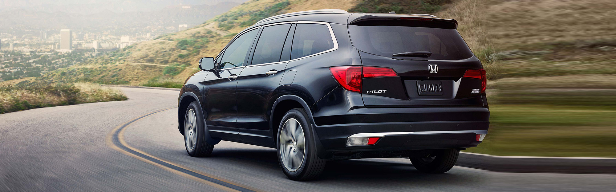 A black 2019 Honda Pilot drives down a country road toward the big city