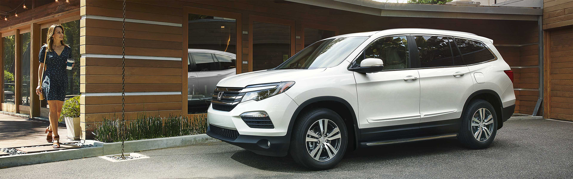 A white 2019 Honda Pilot, parked in front of a trendy home, while its driver walks over to take a ride