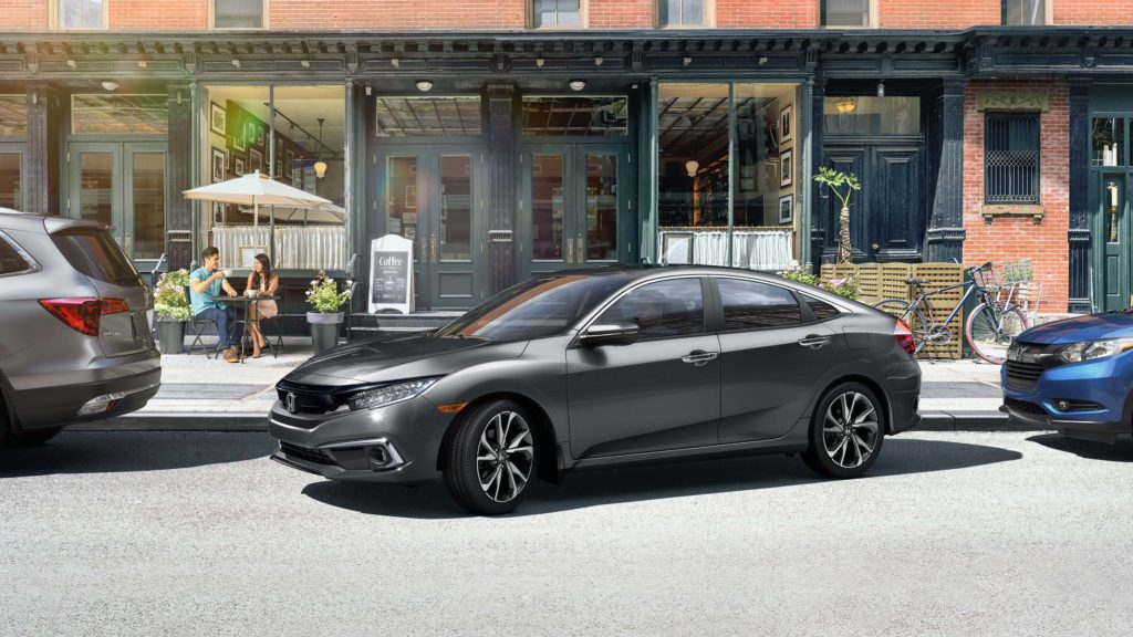 A charcoal 2019 Honda Civic backing into a parallel parking space
