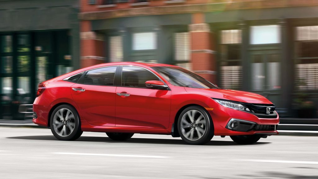 A red 2019 Honda Civic Sedan cruising down a city street