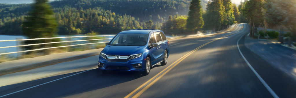 A blue 2019 Honda Odyssey cruises efficiently down a country highway