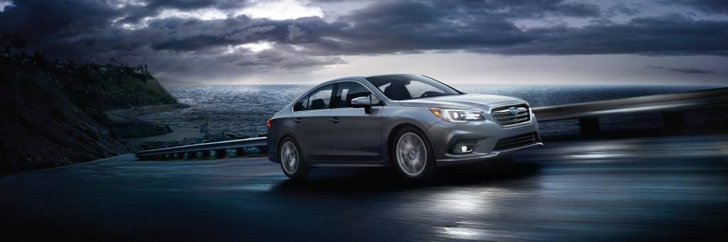 Grey Subaru Legacy in motion uphill at nighttime showcasing Eyesight technology