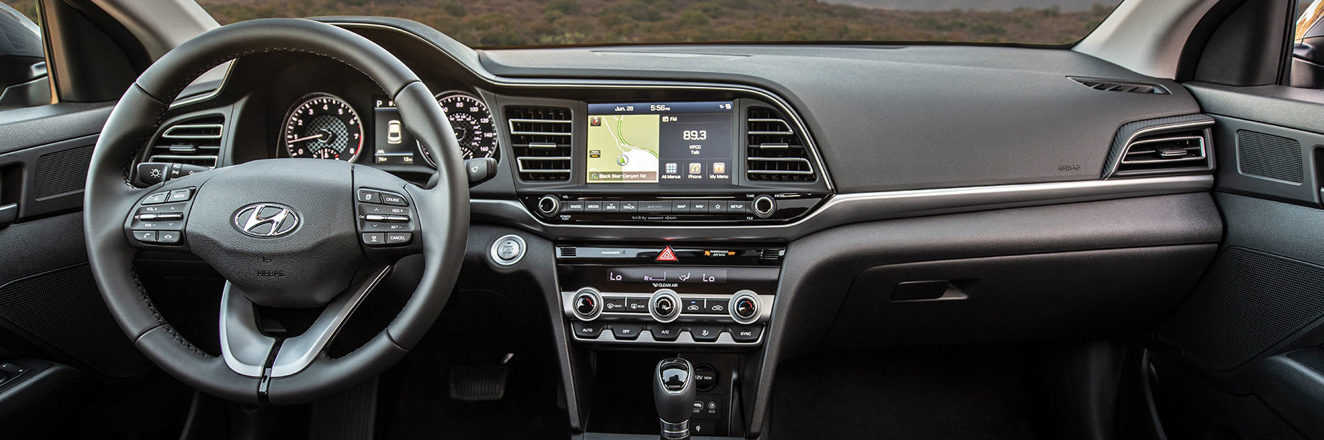 Front interior shot of Hyundai Elantra featuring steering wheel and dashboard