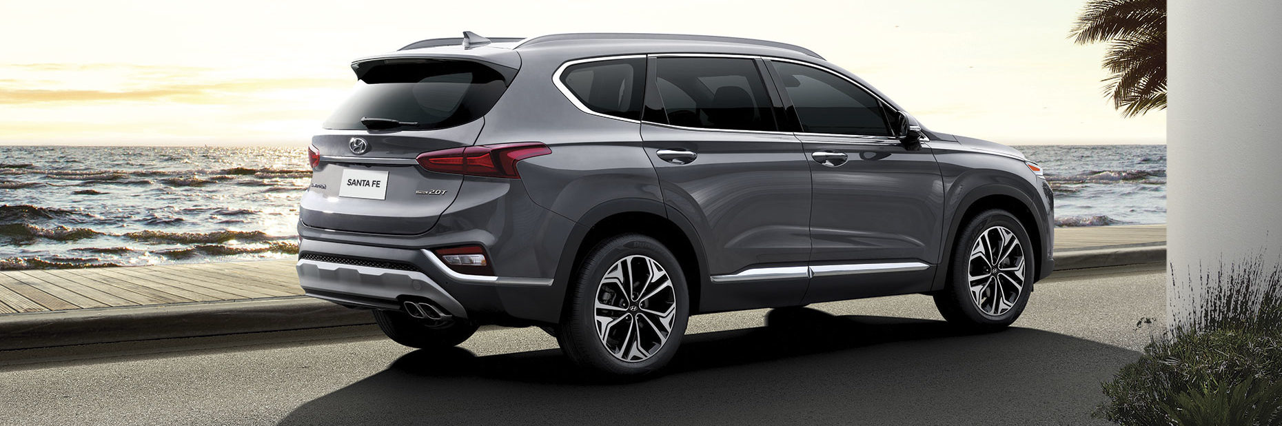 Grey 2019 Hyundai Santa Fe by the waterside as waves cascade and the sun sets