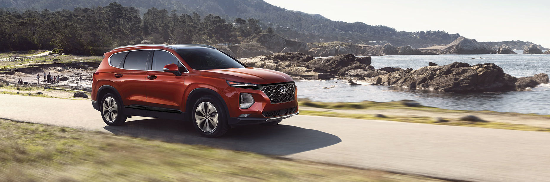Red Hyundai Santa Fe in motion with beach and body of water in background