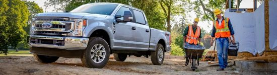 Two construction workers moving cargo near parked 2021 Ford Super Duty X L T F 2 50 Crew Cab with available FX4 Off Road Package in Iconic Silver