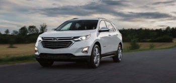 A white 2019 Chevy Equinox roars down a country road