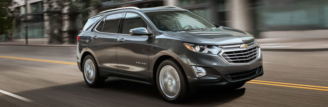 A shiny new 2019 Chevrolet Equinox cruises down a city street