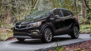 A stylish, black 2019 Buick Encore, parked in the woods