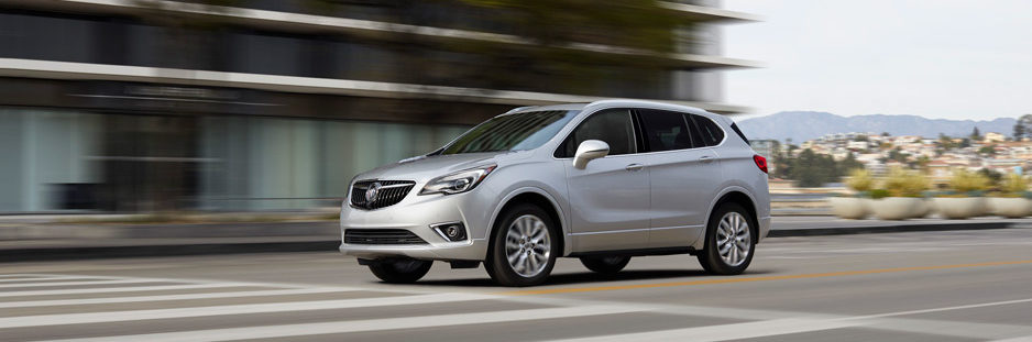 A silver 2019 Buick Envision speeds down a city street