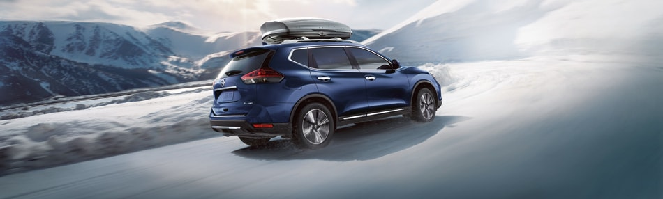 2019 Nissan Rogue in navy blue driving in the snow