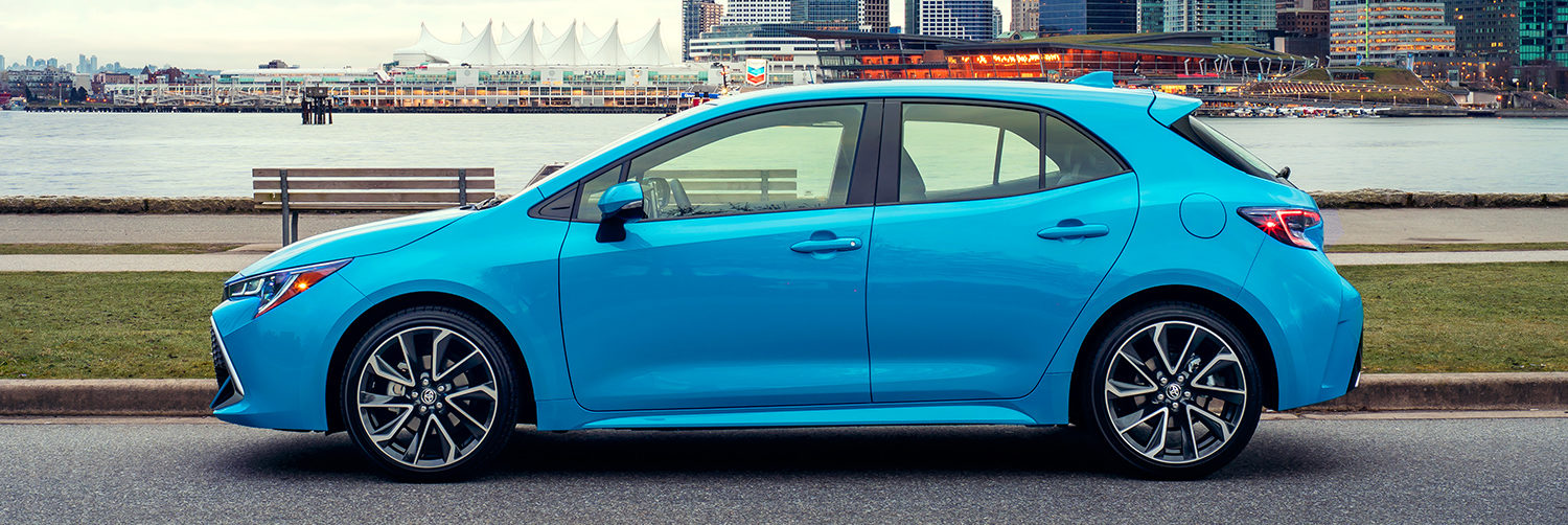 Side shot of Corolla Hatchback in Blue Flame overlooking grass and harbour