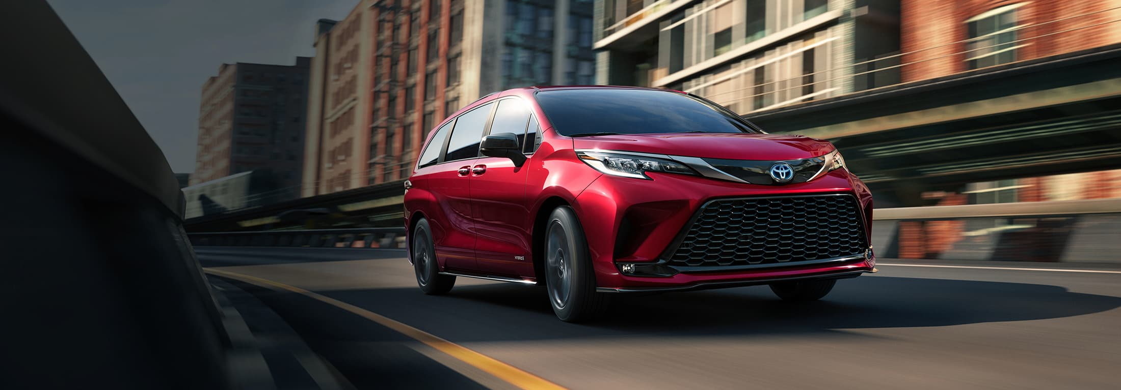 2021 Red Toyota Sienna driving on the road.
