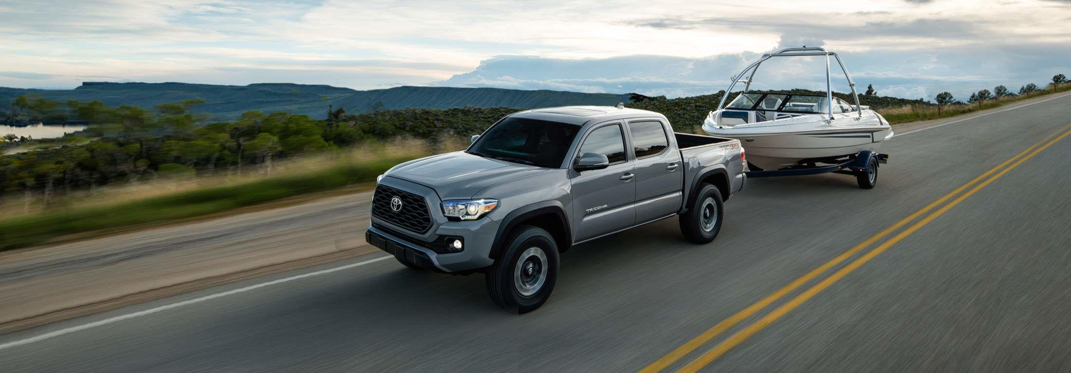 2021 Silver Toyota Tacoma, driving on the road towing a motorboat.
