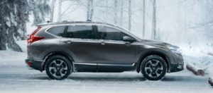 A steely coloured 2019 Honda CR-V sits parked in an icy forest parking lot, undaunted by the snow