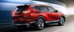 A red 2019 Honda CR-V cruises effortlessly around a corner in an urban tunnel