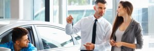 salesperson-giving-keys-to-new-car-owners (1)