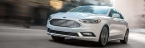 A white Ford Fusion Energi driving along a city street