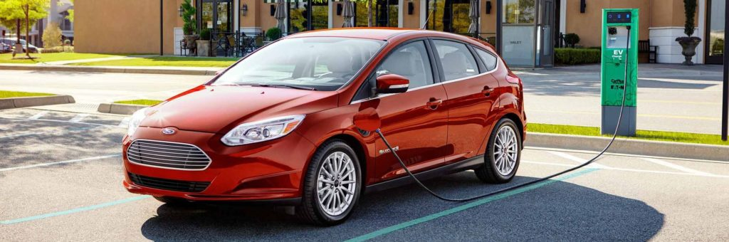A red Ford Focus Electric, plugged into a charging station in a parking lot