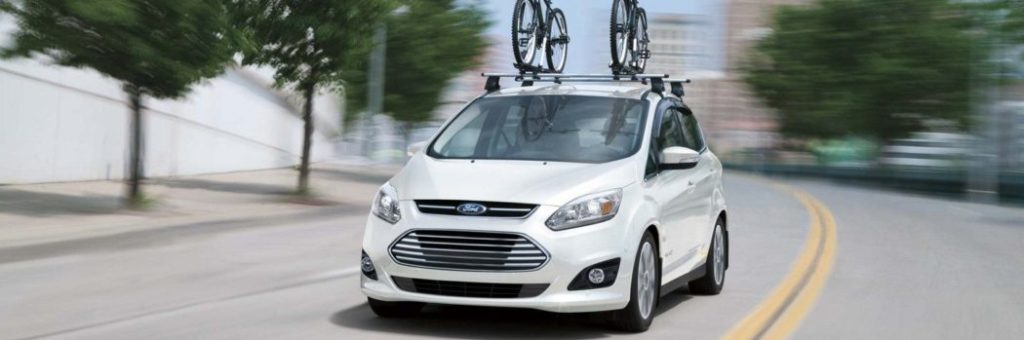A white Ford C-MAX Hybrid with bike rack, cruising down the street.