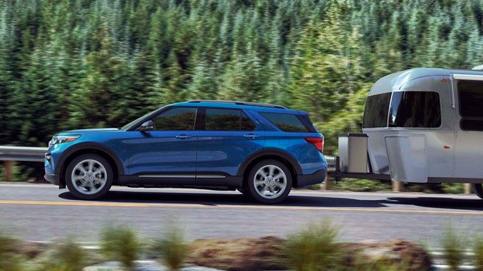 2020 Explorer Platinum Hybrid in Blue towing a trailer on the highway
