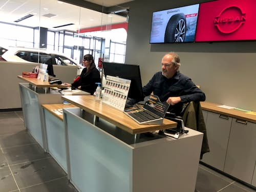 Male and female Receptionists at the front desk inside Nissan dealership