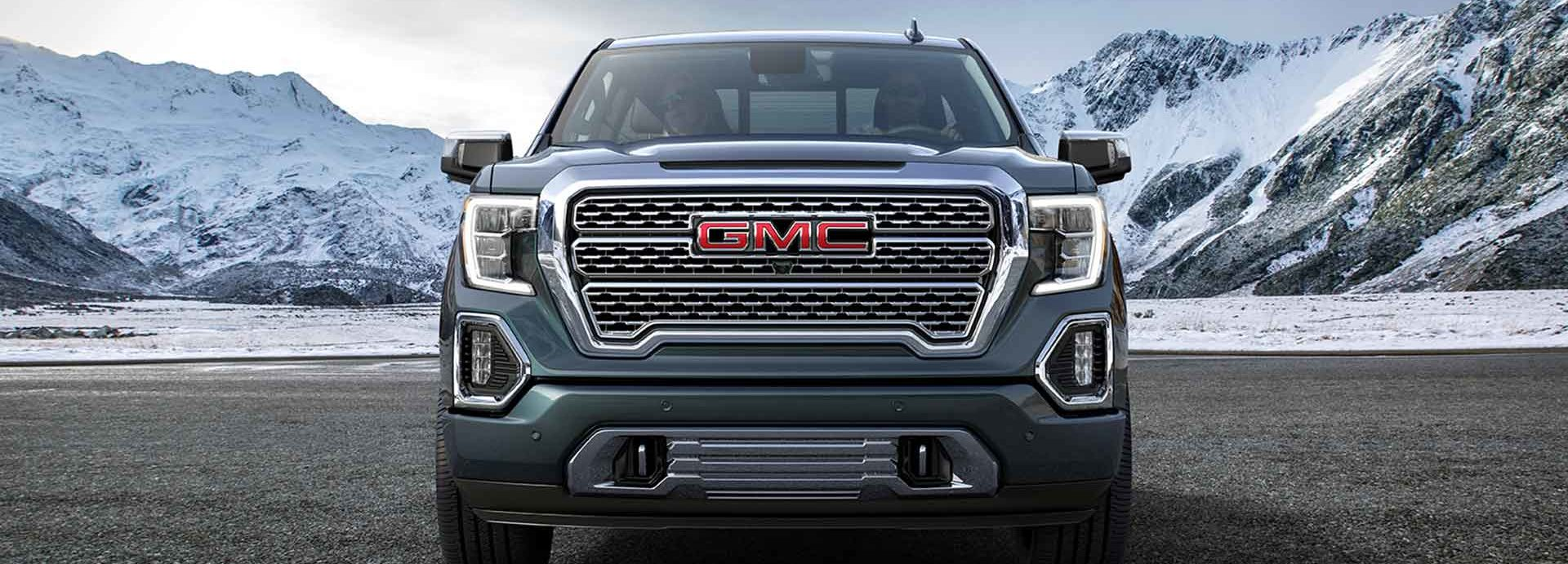 The 2019 GMC Sierra AT4 parked in the middle of an open soil field with a backdrop of mountains