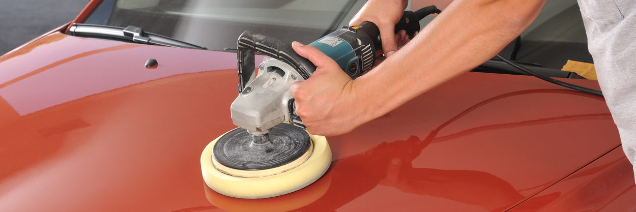 Close up of technician waxing car with polisher
