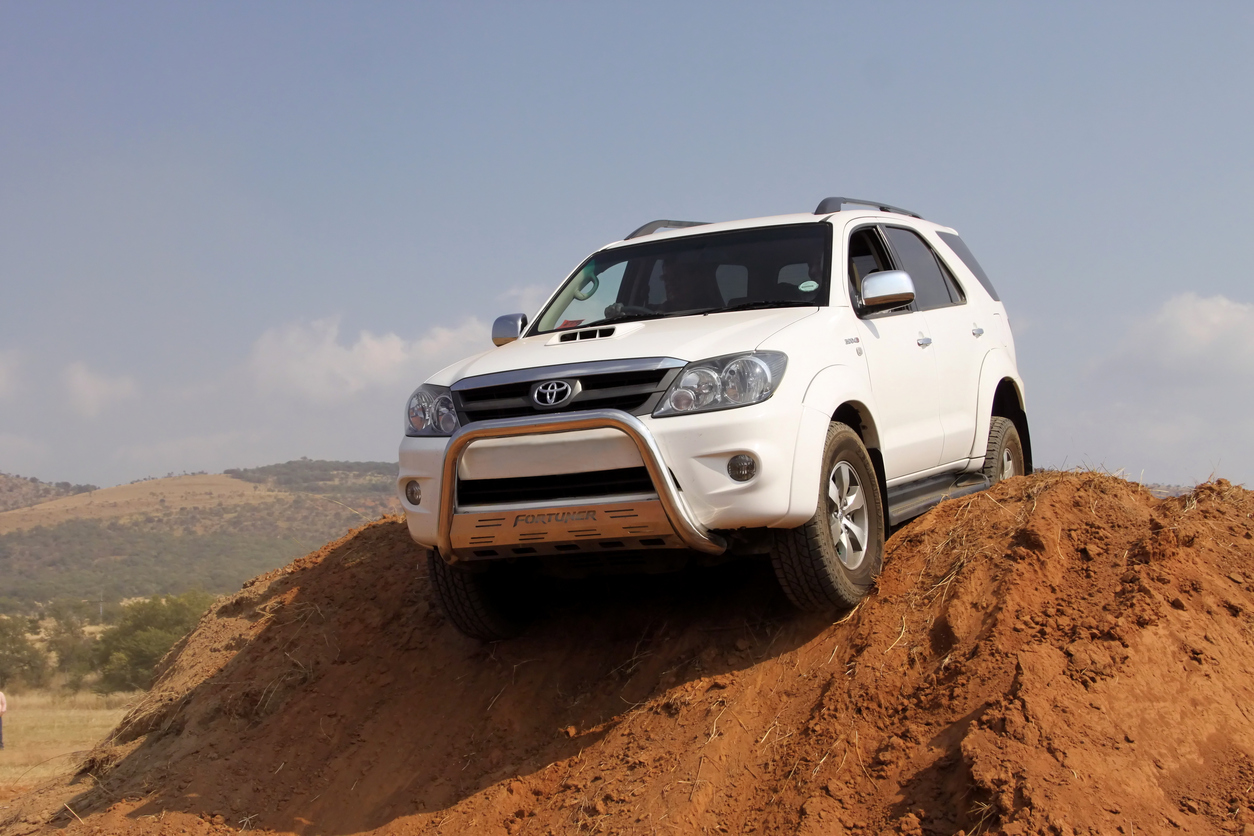 White Toyota Fortuner going over dirt hill