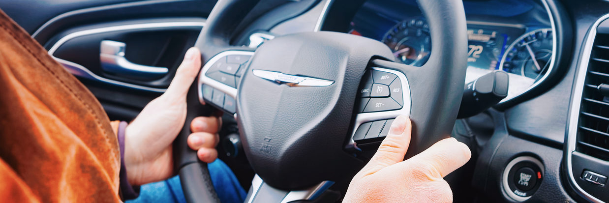 Man hands holding steering wheel of Chrysler car