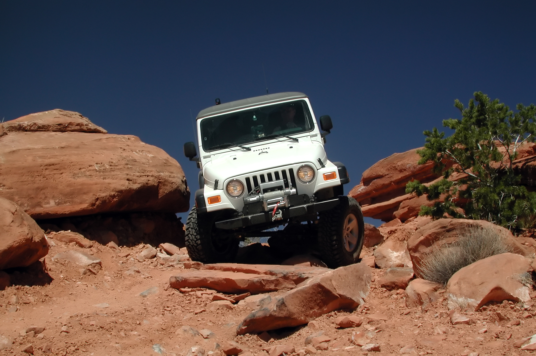 Jeep Rubicon III driving over large, rocky terrain
