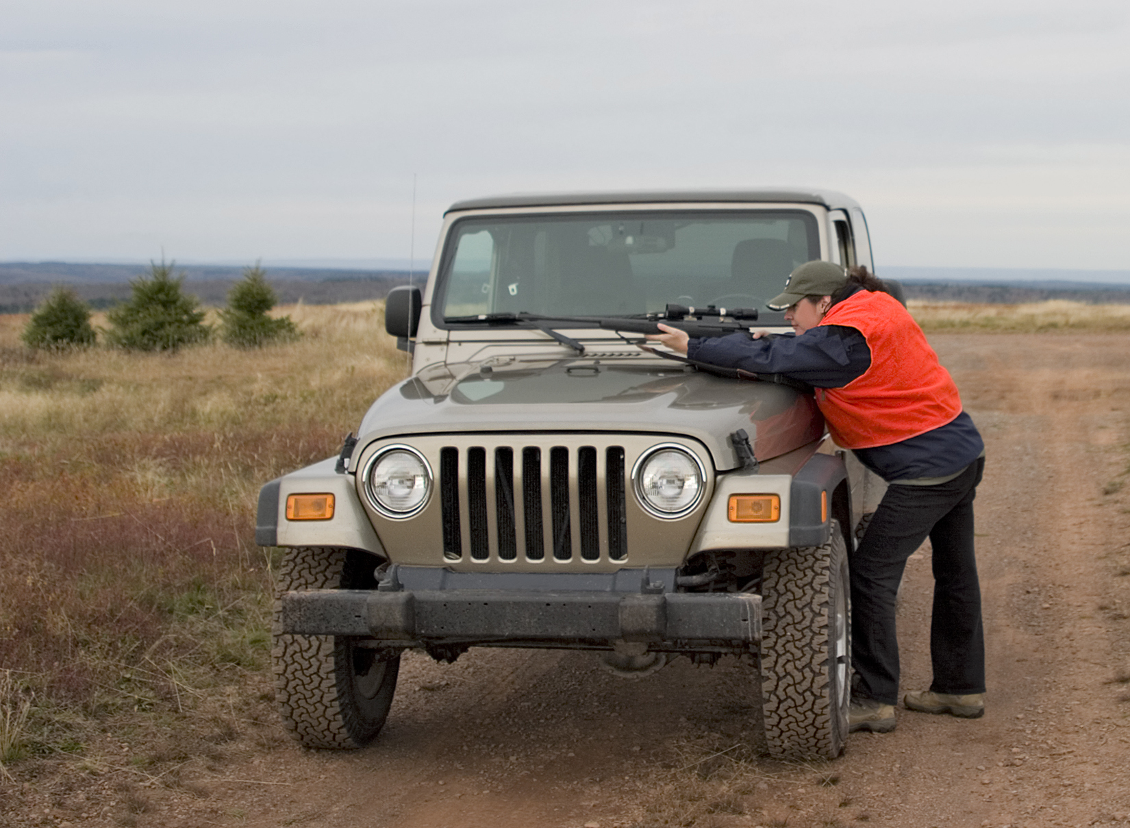 Woman hunter leaning over 4x4 Jeep with a gun