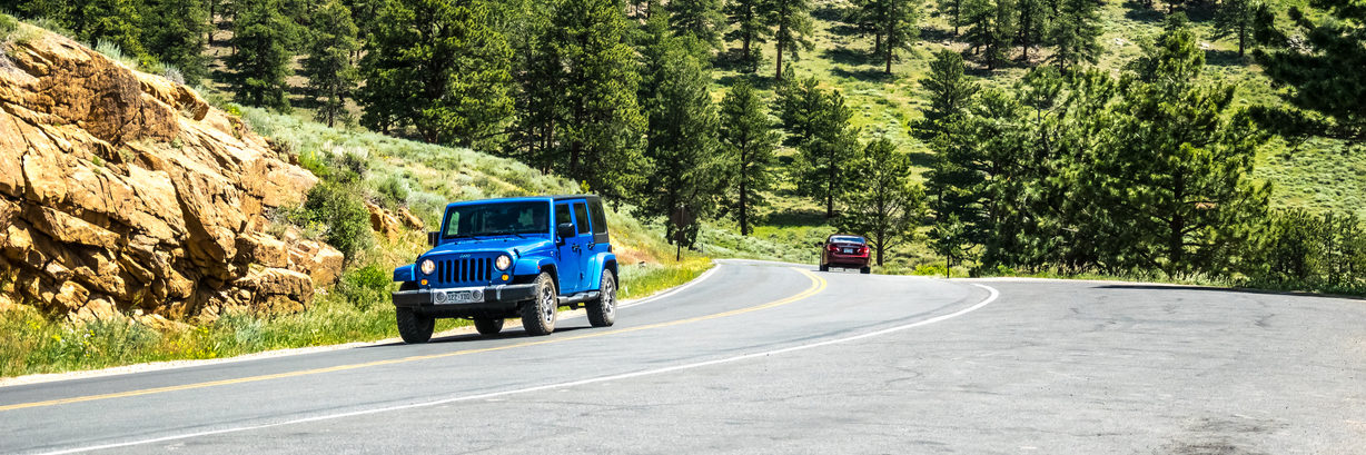 Jeep Wrangler on a winding mountain road in the Rocky Mountain National Park