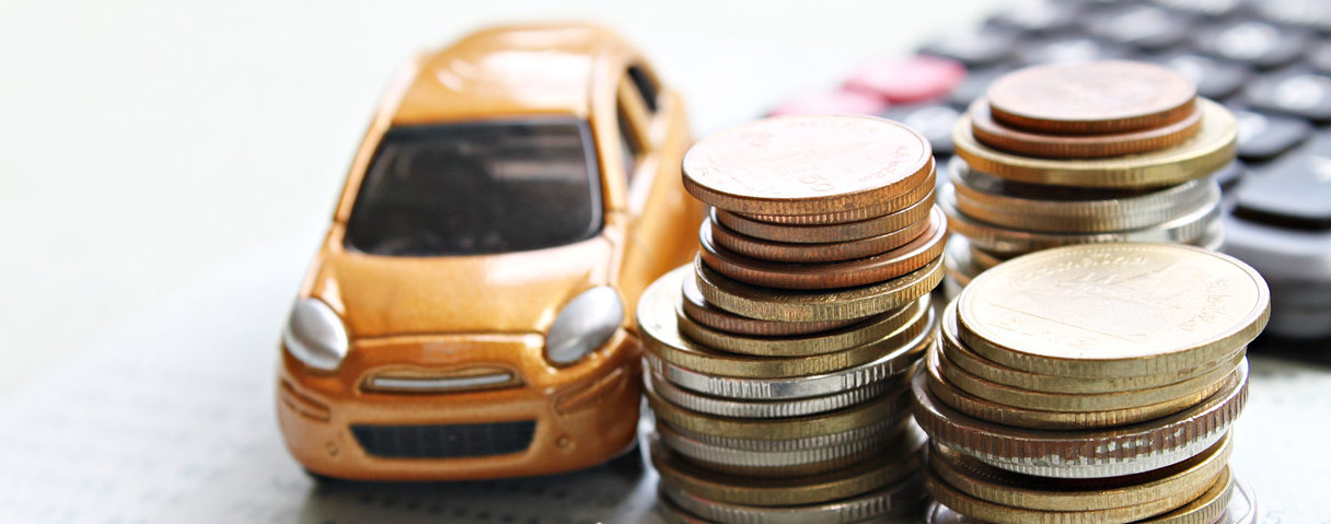 Miniature car model, coins stack, calculator and saving account book on office desk table