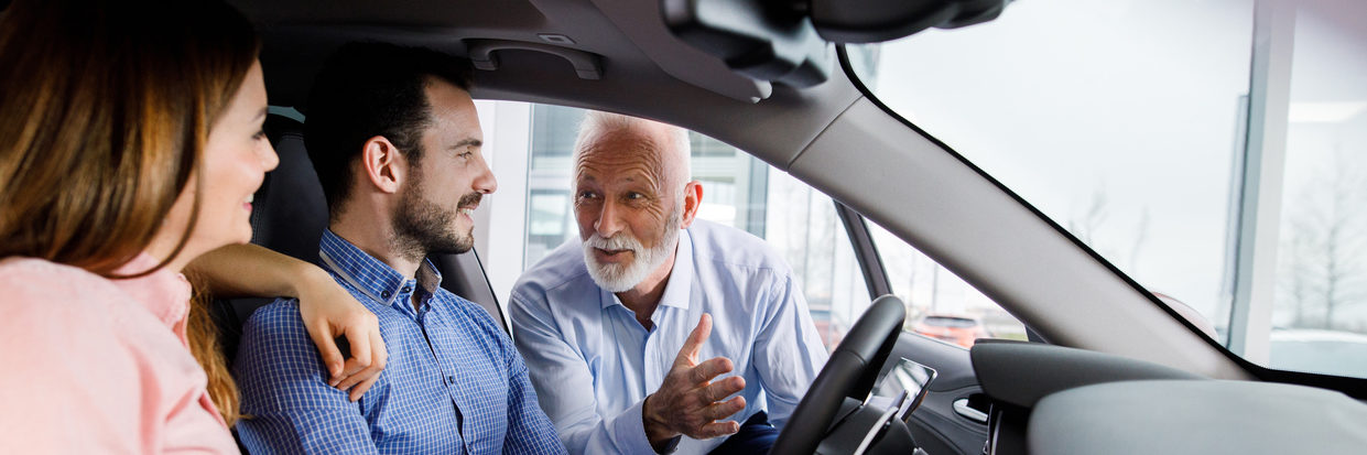 Vehicle dealer selling new car to young couple