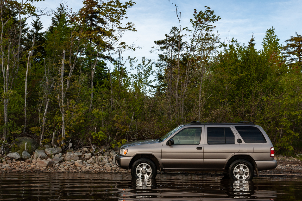 Nissan Pathfinder parked in water and beside trees