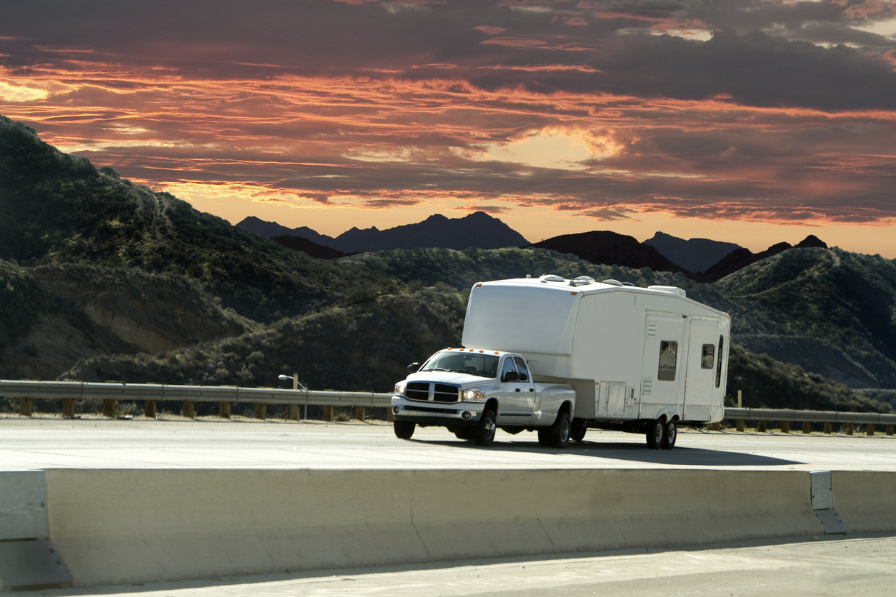 Truck hauling a camper trailer in front of a sunset