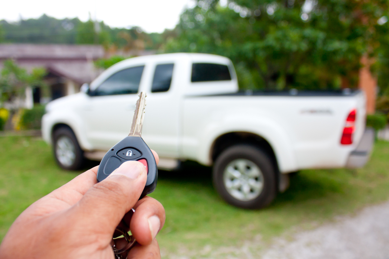 Close up hand holding car key in front of a truck