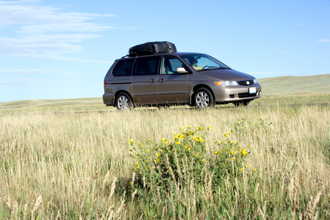 Minivan with cargo on top in a field