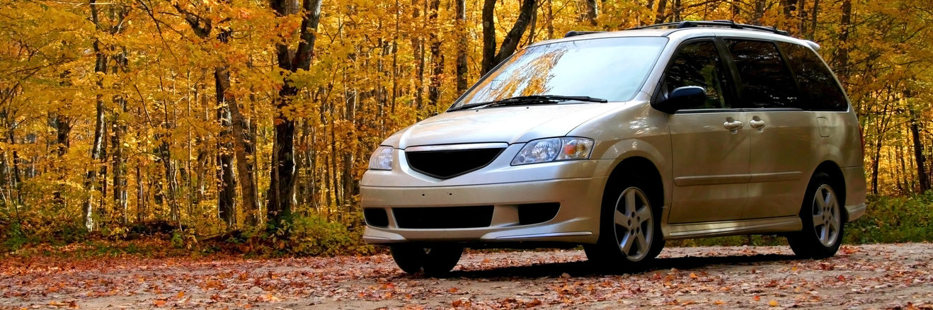 Minivan in front of autumn trees