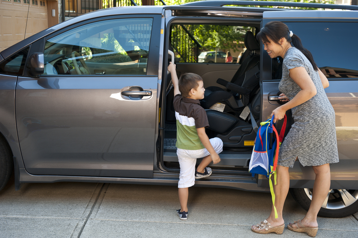 Child stepping into a minivan
