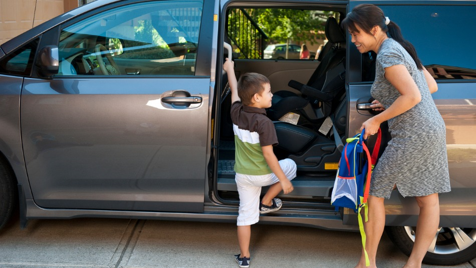 small child getting into minivan while mother oversees