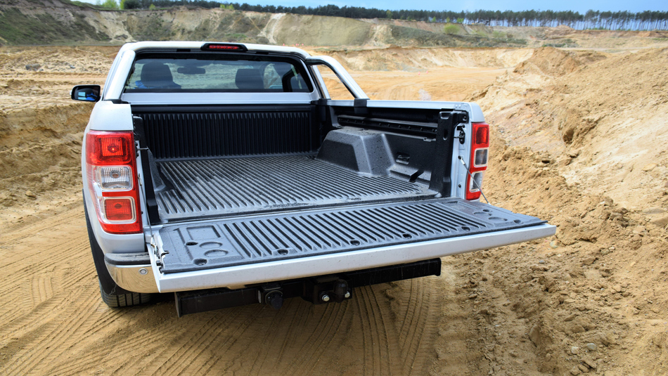Empty cargo bed in white Ford Ranger, parked on gravel/sand road.