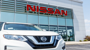 Front of new white Nissan SUV parked in front of dealership window, large red block letters spell out Nissan