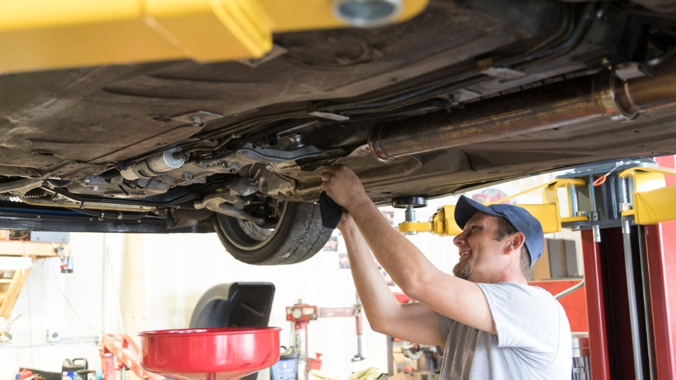 mechanic in white shirt and blue hat works on the undercarriage of a vehicle