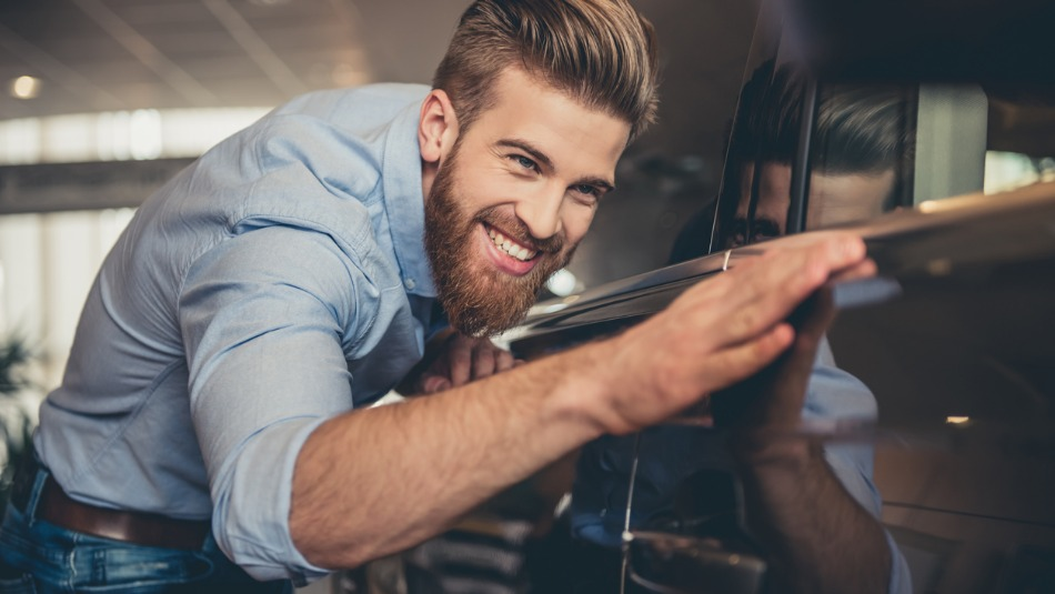 man smiling while he intently checks the detail of a car door