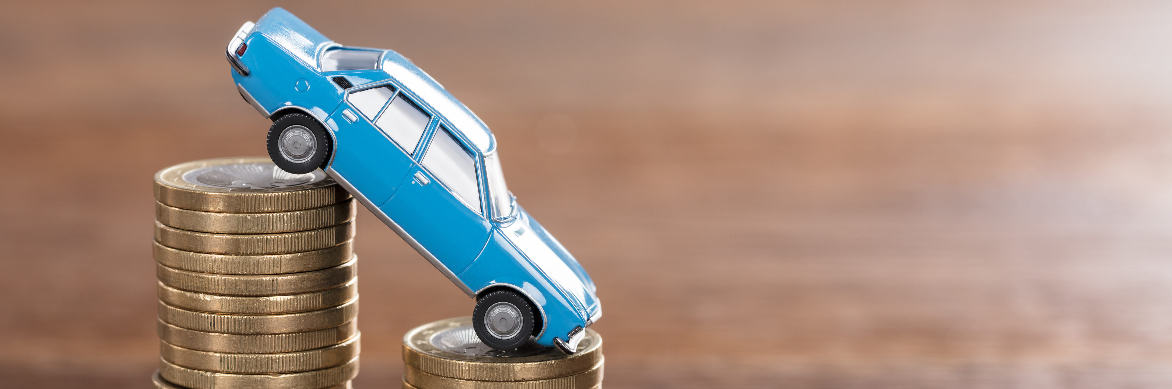 Close-up Of A Car Model Over A Stacked Coin At Wooden Desk