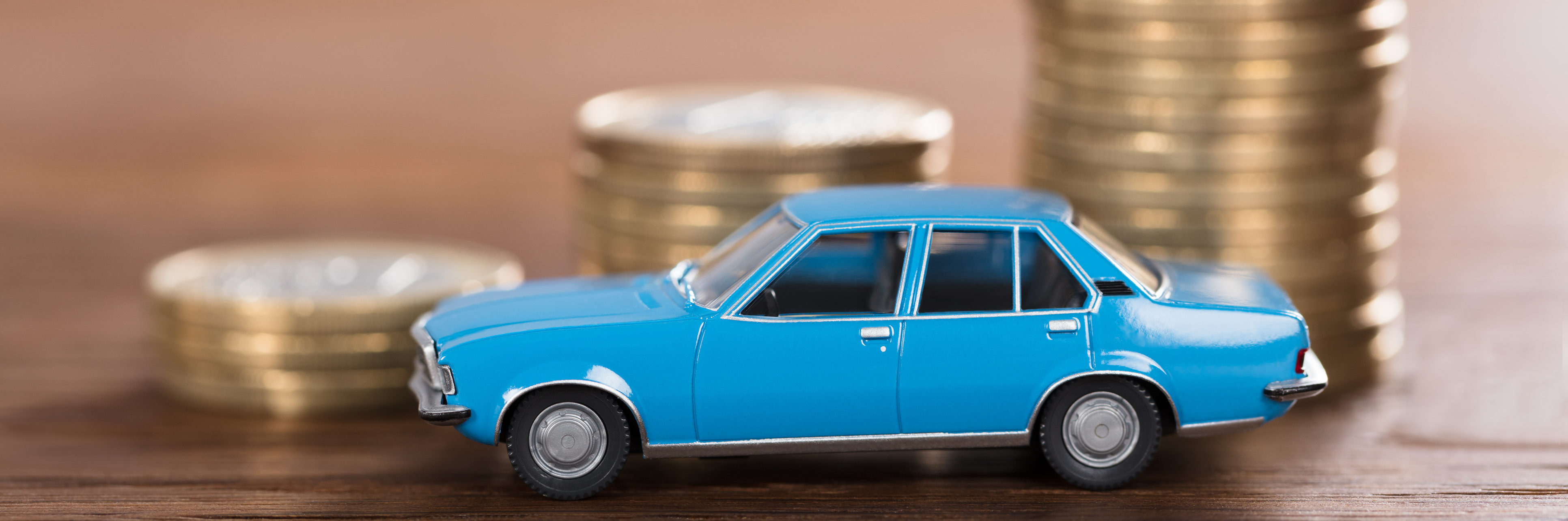 Close-up Of A Car Model In Front Of Stacked Coin At Wooden Desk